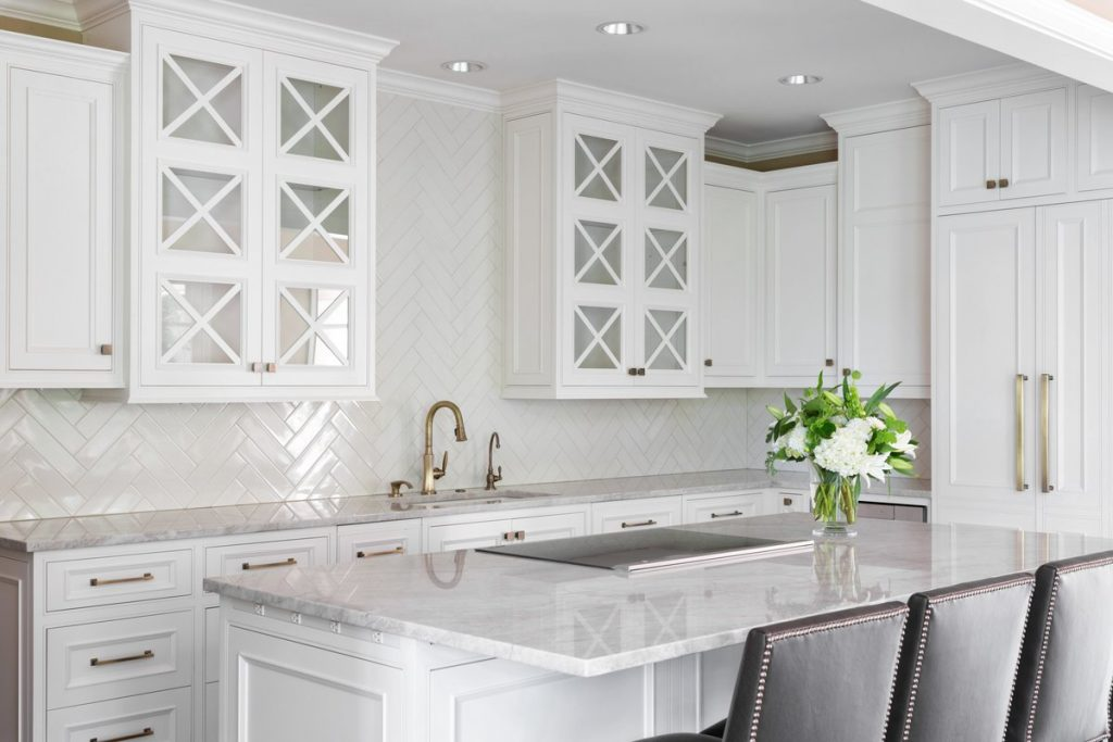 White kitchen with brass accents, brass faucet, and quartz countertop